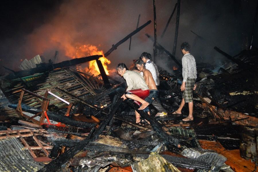 Men battle a fire raging in Phnom Penh's Meanchey district. (Alex Consiglio/The Cambodia Daily)