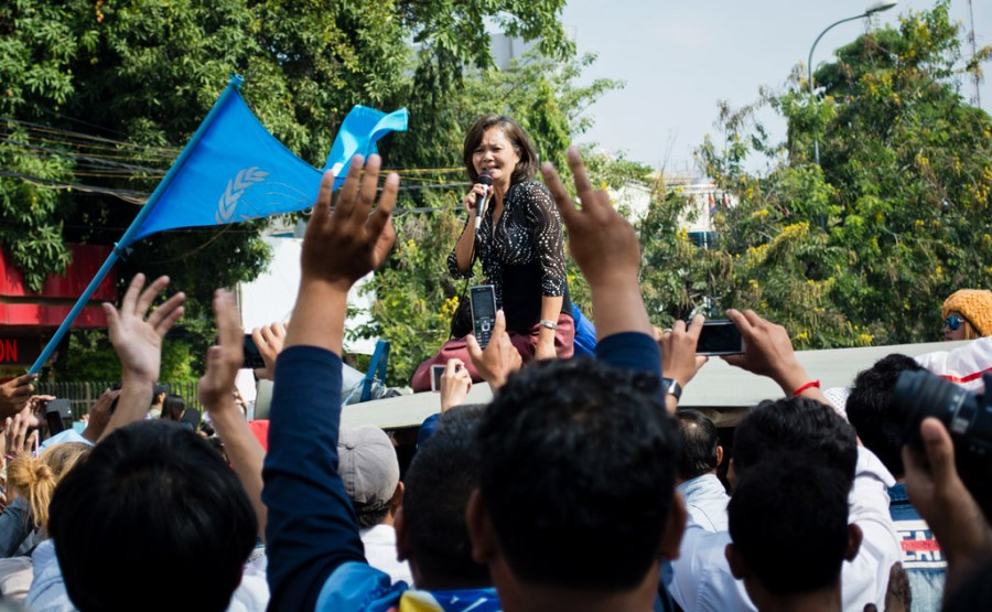 Mu Sochua, atop a tuk-tuk, revs up CNRP supporters outside the Phnom Penh courthouse. // Alex Consiglio