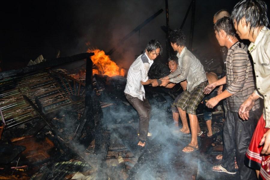 Men battle a fire raging in Phnom Penh's Meanchey district. // Alex Consiglio/The Cambodia Daily