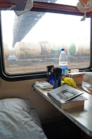 na stoliku zestaw podstawowy: kubek termiczny, zwilżane chusteczki i książka, a przy okazji widać jak czysta była szyba