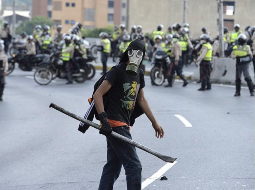 Un homme se dirige vers la police, à Caracas. Dans ce pays pétrolier dont l'économie s'est effondrée avec la chute des cours du brut, la majorité des aliments et médicaments sont aujourd'hui introuvables.