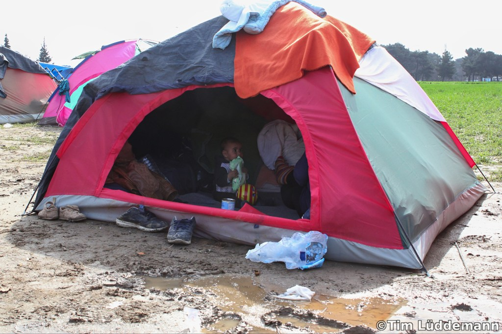 Child sits in a tent in the middle of the mud