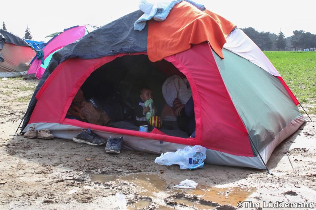 Kind sitzt in einem Zelt mitten im Schlamm