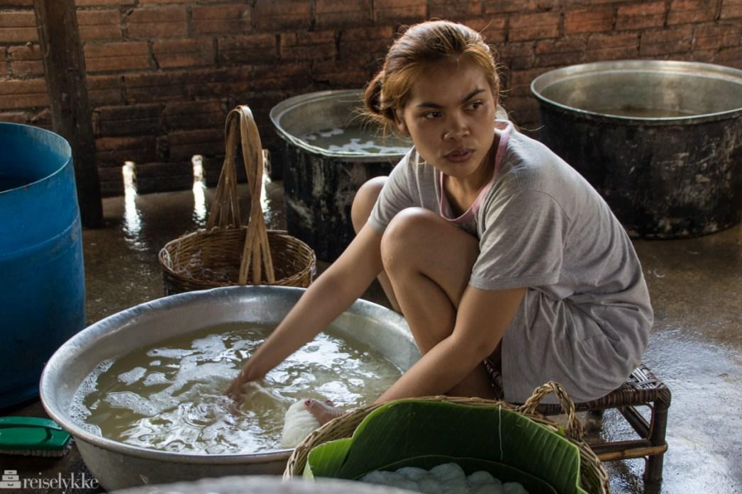 Ung kvinne lager nudler i Kampot
