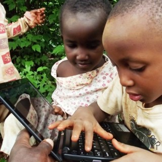 Elvis Muraguri and his friend play with his uncle's laptop outside his home. Computers have now become an essential part of education. [Picture: Robert Nyagah]