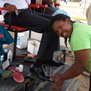 Sheila Wamoita shining a client's shoes at her work station.She joined the business due to lack of employment but has never regretted the bold step that she took.Picture:Carolyne Oyugi