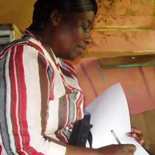 Lucy Ndirangu marking her register as she prepares to make her next round in Mwiki,Kasarani.Picture:Joyce Chimbi