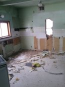 With the cabinets gone we hacked through the wall into the bathroom on the other side.