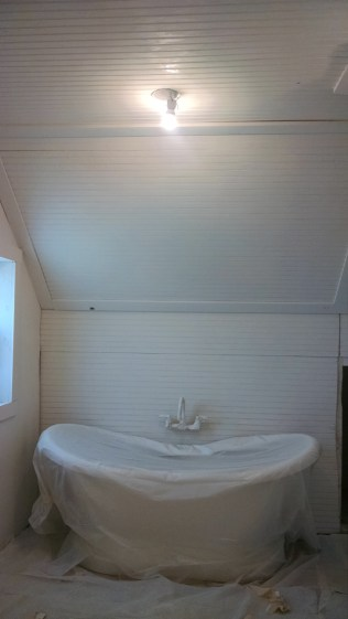 My bathtub still all wrapped up, looking spectacular against a wall of white bead board!