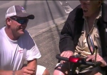 Man helps elderly gentleman, after his motorized chair stalls in road.
