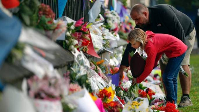 Mourners lays flowers on a wall at the Botanical Gardens in Christchurch.
