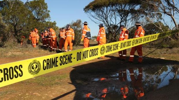 Police and SES search for evidence near where the suitcase was found.