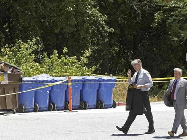Investigators walk past rubbish and recycling bins behind crime scene tape at the Tannery