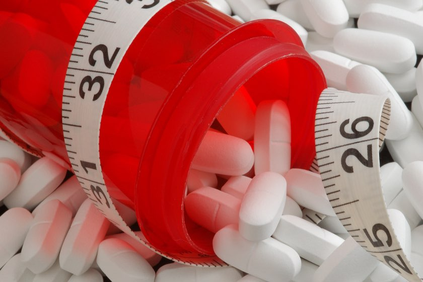 Spilled prescription pill bottle wrapped with tape measure