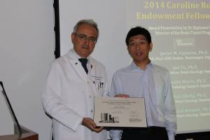 Raymond Sawaya, director of MD Anderson's brain tumor program, presents Jun Fu with the 2014 Caroline Ross Endowment Fellowship.