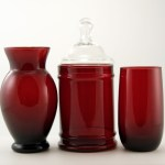 In Anchor Hocking's patented Royal Ruby glass color. Set includes: (1) covered canister just the right size for vanity items; (1) a vase for your posies; and (1) matching tumbler