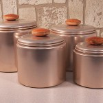 Well-preserved early 1950's Mirro aluminum canister set in light metallic pink with copper -like interior.
