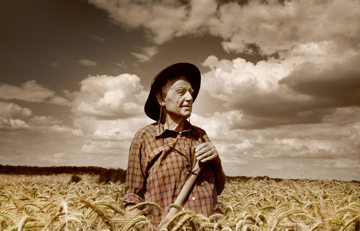 Old photo of happy senior peasant after hard work in the field