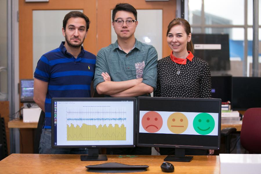 From L-R: PhD Fadel Adib, PhD Mingmin Zhao and Professor Dina Katabi demonstrating different 'emotions' like the picture. Credit: Jason Dorfman, MIT CSAIL