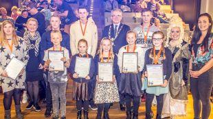 De voormalig wethouder cultuur Trees van der Paard (tweede van links) burgemeester Koen Schuiling (staand rechts midden) tussen de winnaars van de jeugdlintjes in 2017 (foto Peter van Aalst)