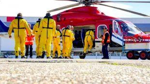 Werknemers stappen op een door DHSS ingehuurde helikopter op de luchthaven (foto DHA)