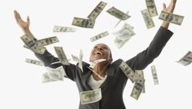 African American businesswoman throwing money in the air