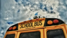 Close-Up High Section Of School Bus Against Clouds