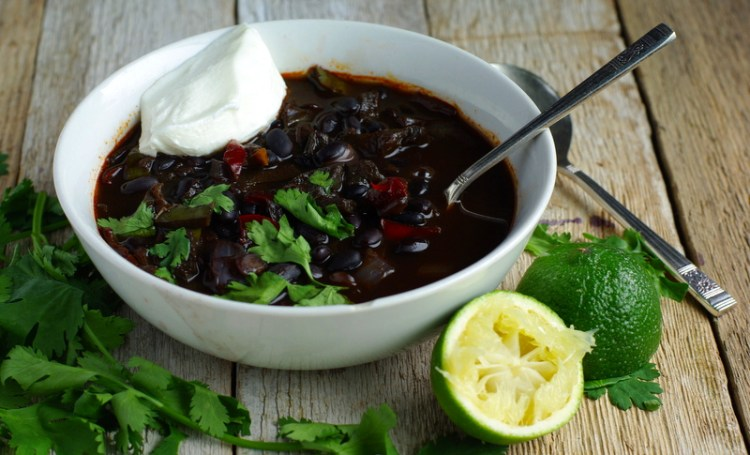 Bowl of black soup filled with glossy black beans, shreds of red pepper and topped with fresh green coriander leaves and a dollop of yogurt.