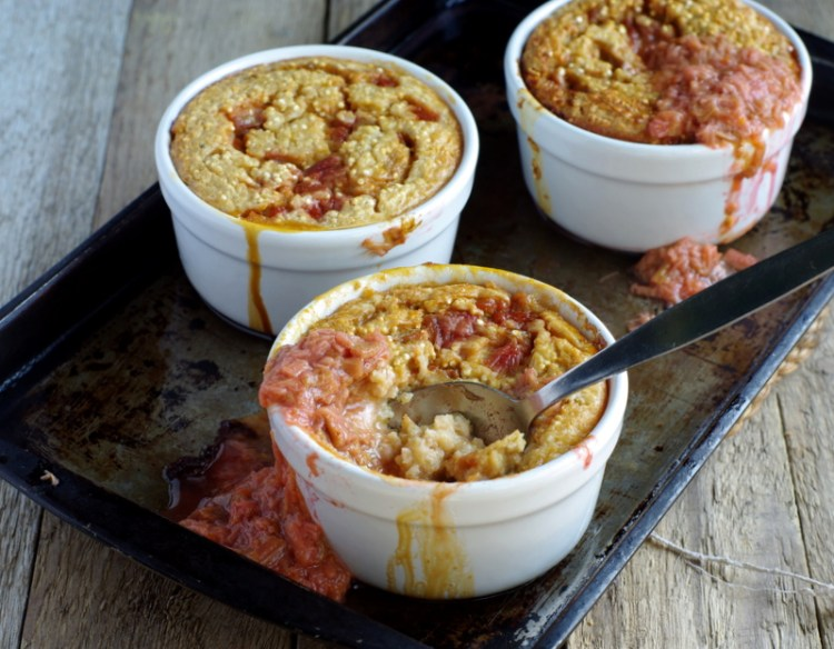 Three small bowls filled with golden baked porridge and oozing with rhubarb.