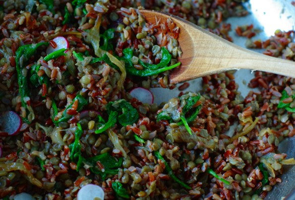 Red rice with bright green leaves running through it.