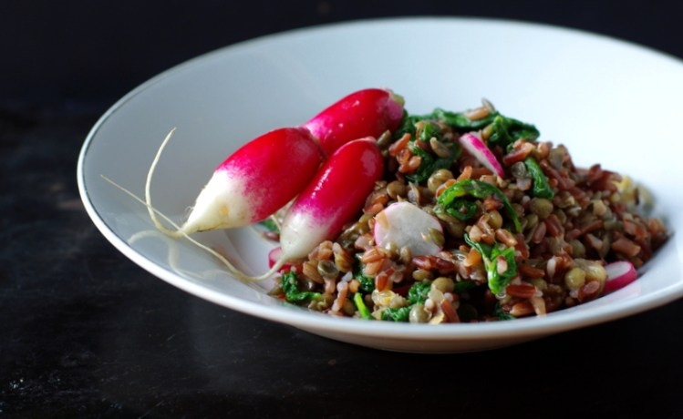 A bowl of red rice with green leaves running through it, topped with three bright, fresh radishes.