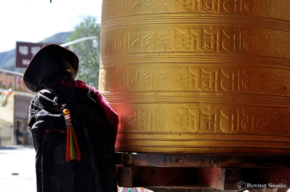 Tibetan woman turning a giant prayer wheel