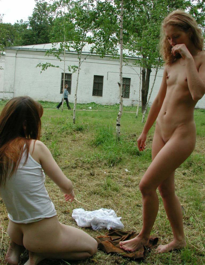 Two naked girls posing in front of church