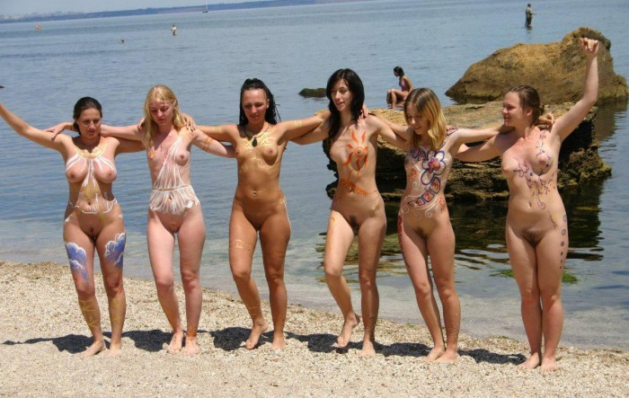 Hot six girls showing their nude painted bodies on the beach.
