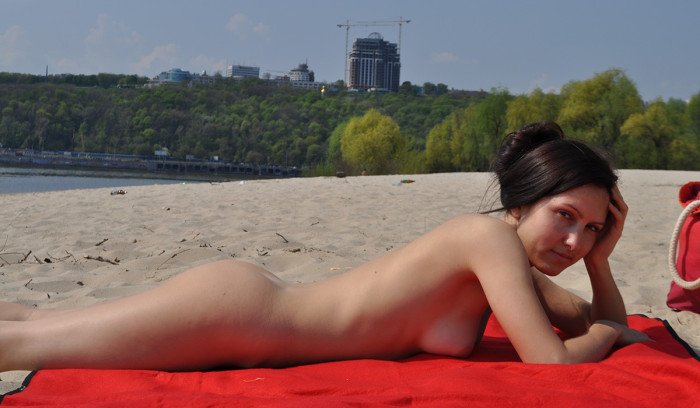 Beautiful brunette posing naked on nudist beach