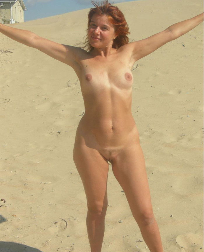 Totally naked MILF is standing in the middle of a hot sunny beach