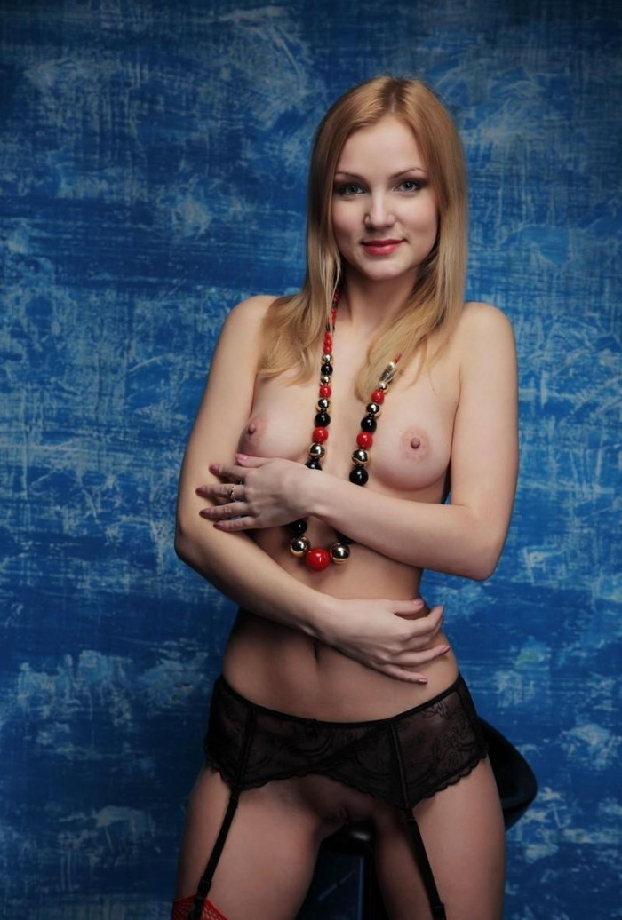 Blonde in red stockings shows shaved pussy