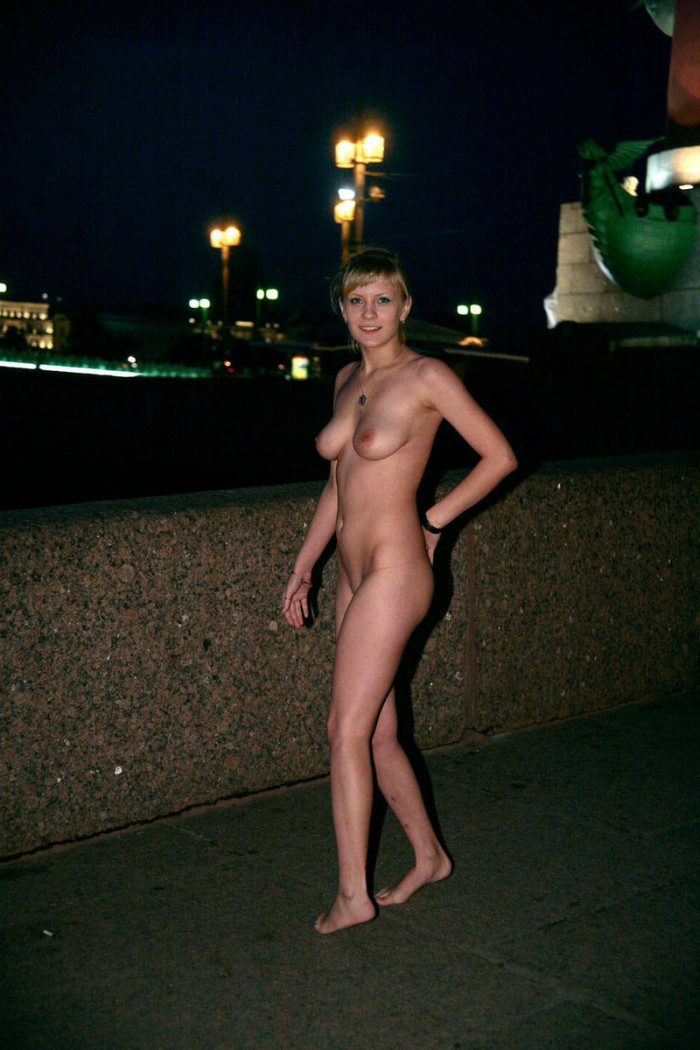 Blonde with a tattoo on the lower back walks naked through the city at night