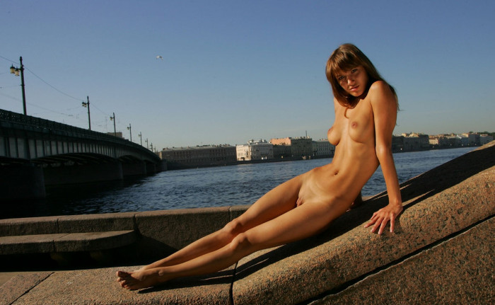 Slim busty girl on the pier in St. Petersburg
