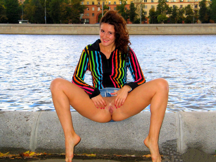 Girl in bright jacket shows pussy in a public waterfront