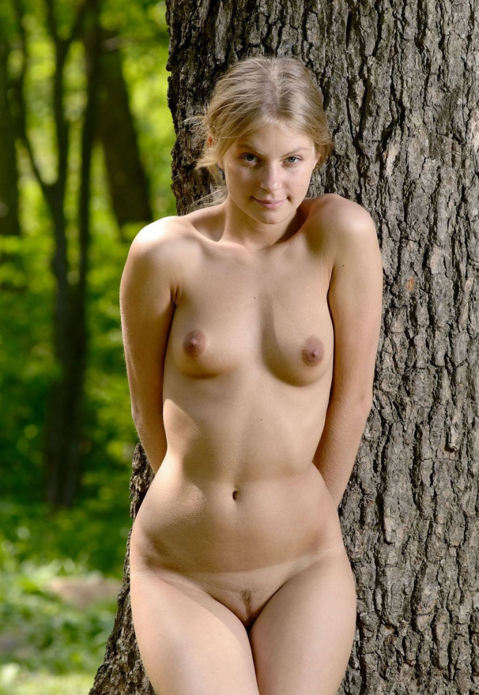 Very sweet blonde posing at green forest