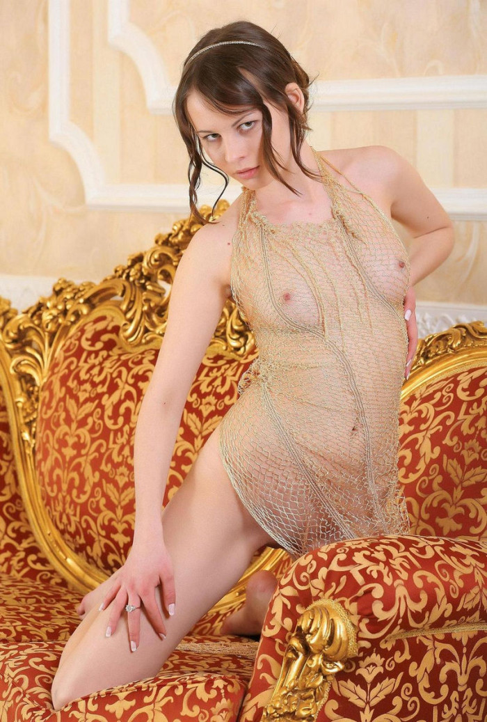 Hot girl in fishnet dress on luxury sofa