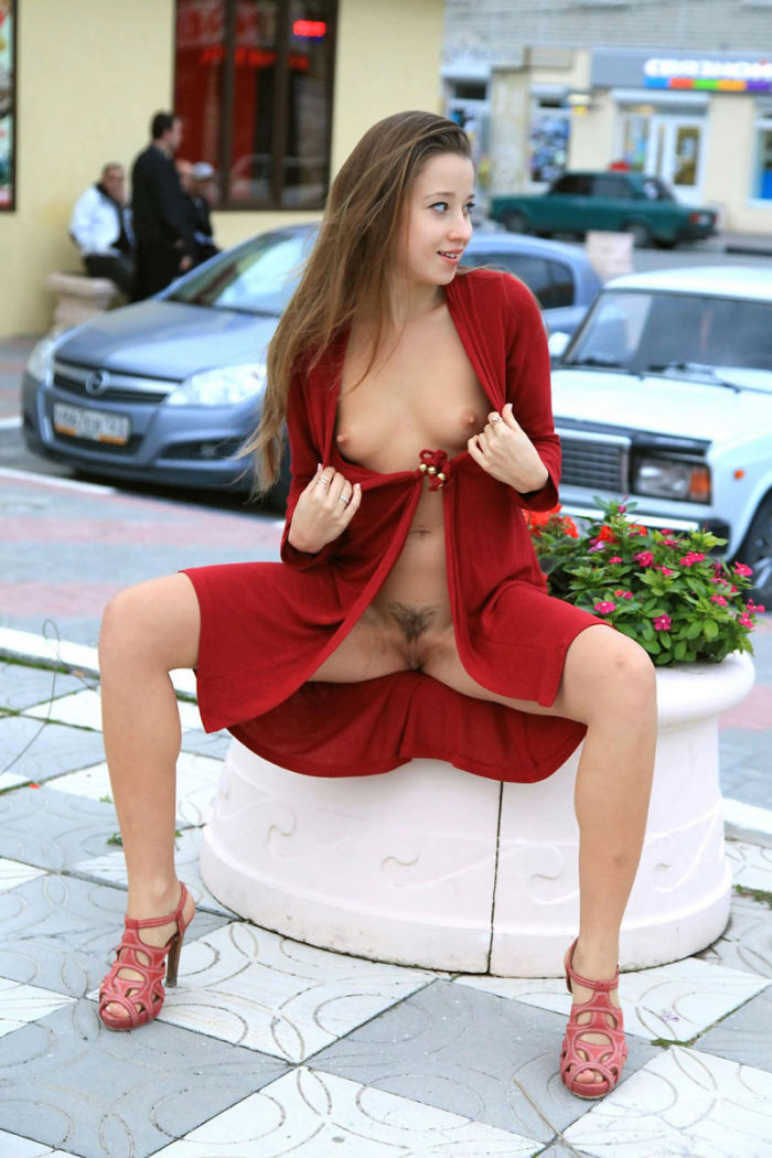 Taissia A posing in red coat in resort town