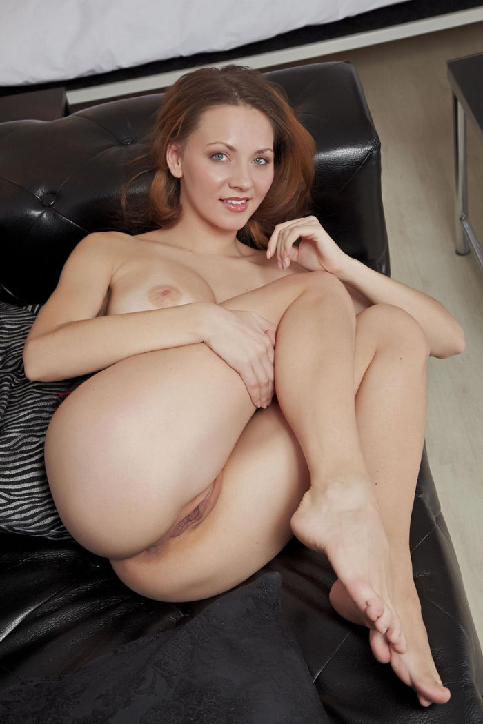 Sexy lady showing pussy on a black couch