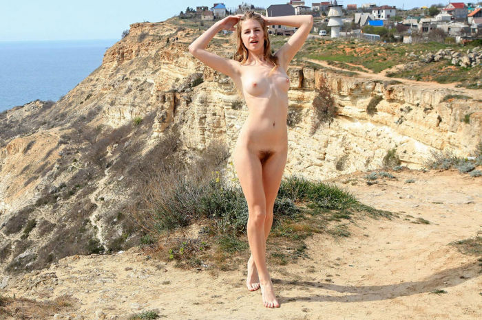 Young girl with furry twat on a steep cliff