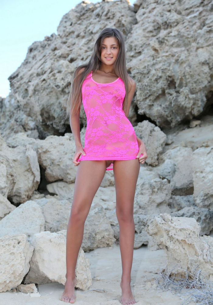 Tanned girl Masha E in bright pink dress on the beach