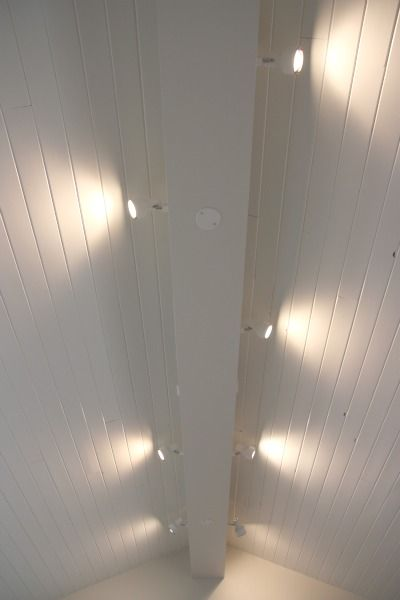 track lighting installed to wash the vaulted ceiling with light and provide indirect ambiance over vertical e