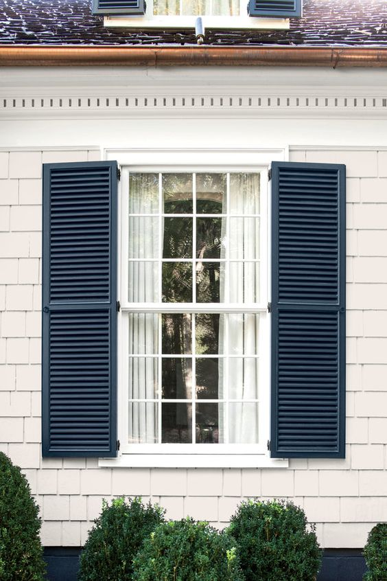 Stong blue shutters on window with white curtains inside the home, white siding on the body of the house