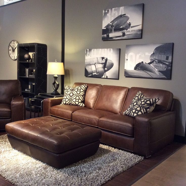 family room with warm gray walls black and white art brown leather furniture decor