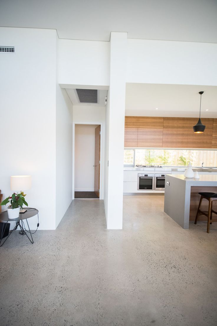 polished concrete flooring concrete kitchen floor Red Tail Homes Sleek Concrete Kitchen White and timber look cabinetry with glass splash back and black pendant lights makes for a beautiful modern kitchen
